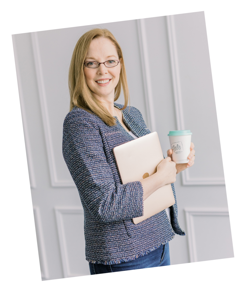 Christine stands in a blue checked blazer smiling at the camera. She is holding a cup of coffee in her left hand and is holding a notebook against her body in her left arm.