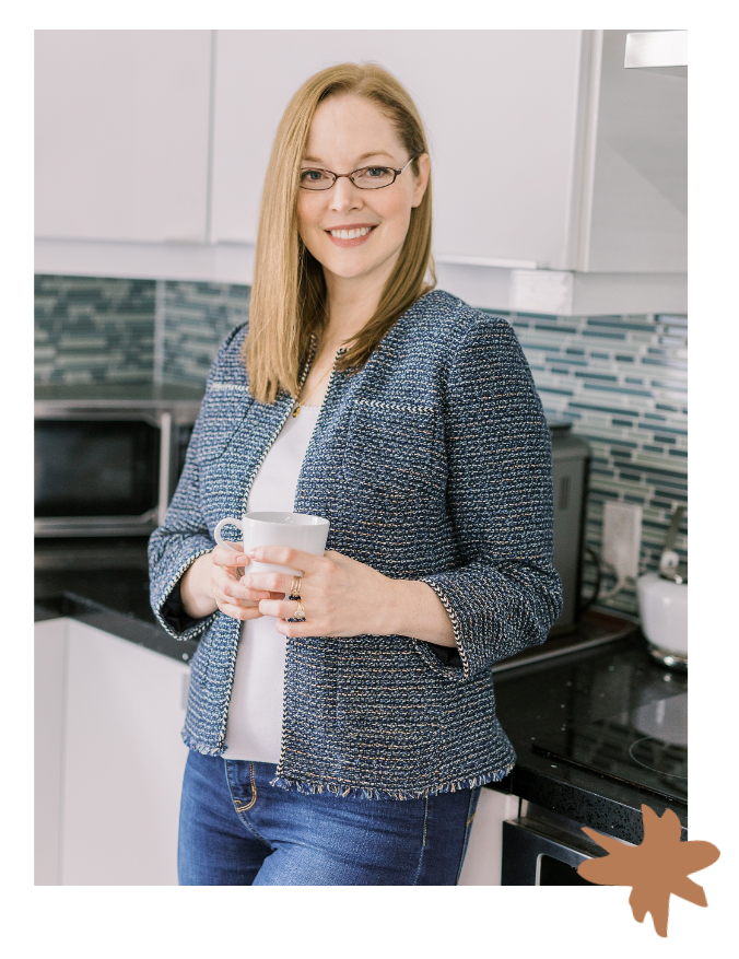 Christine Cowern stands in a kitchen and leans with her back against a counter. She holds a cup of coffee wearing a white shirt and a blue checked blazer. She smiles at the camera.